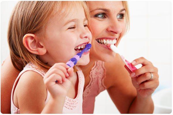 mother daughter brushing teeth college dufferin dental